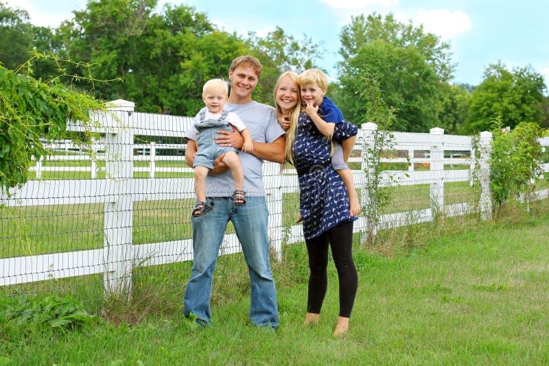 Familia de cuatro miembros feliz afuera imagenes de archivo