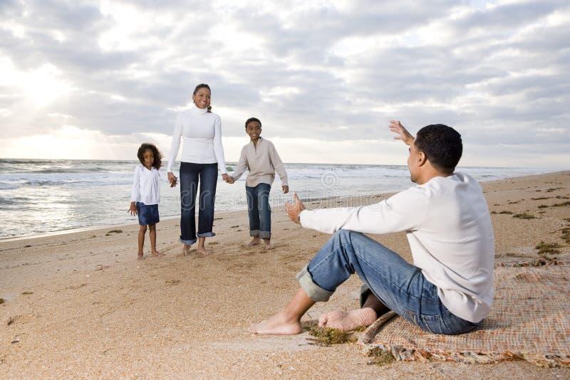 Familia de cuatro miembros feliz del African-American en la playa imagenes de archivo