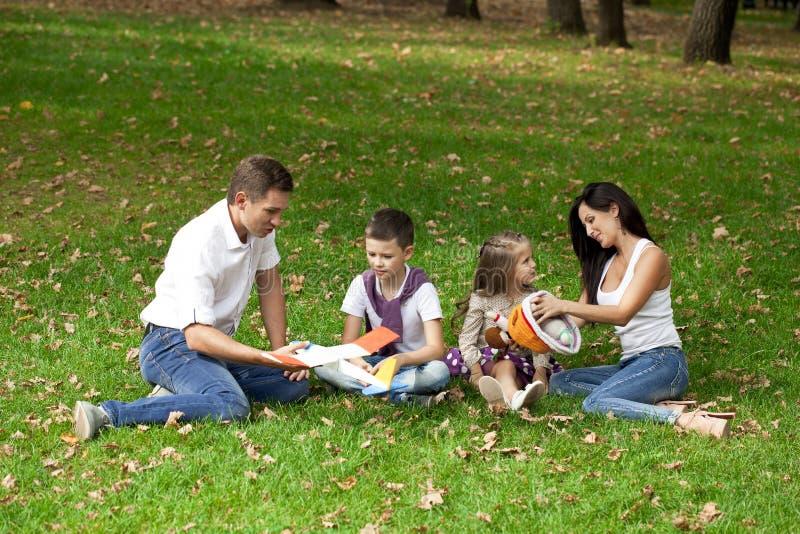 Familia de cuatro miembros feliz, descansando en el parque del otoño fotografía de archivo libre de regalías