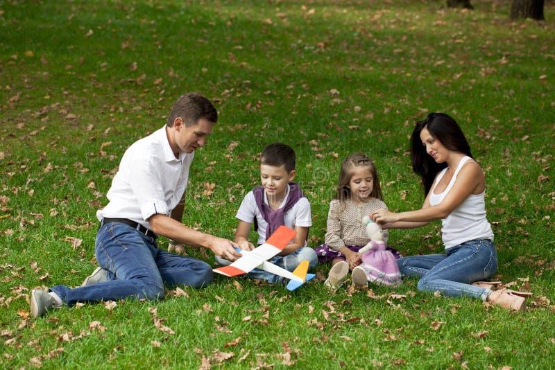 Familia de cuatro miembros feliz, descansando en el parque del otoño imagen de archivo libre de regalías
