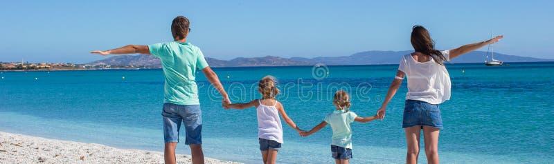 Familia de cuatro miembros feliz durante vacaciones de la playa del verano imagenes de archivo