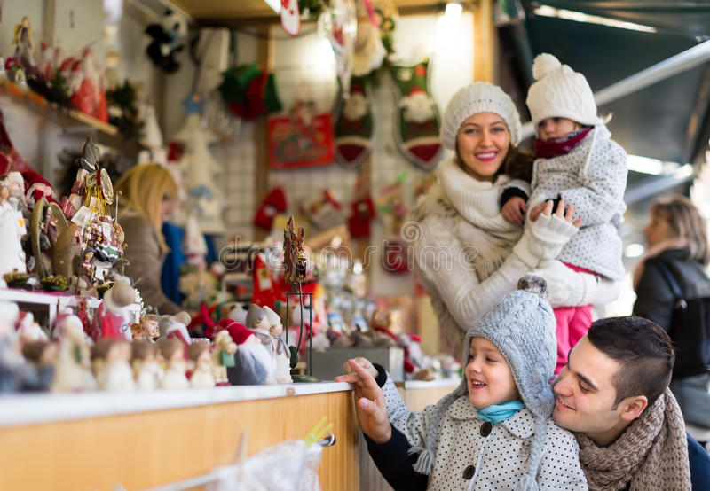 Familia de cuatro miembros feliz en el mercado de la Navidad imagen de archivo libre de regalías