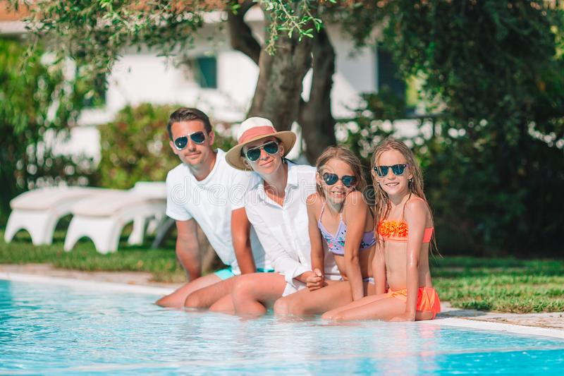 Familia de cuatro miembros feliz en piscina imágenes de archivo libres de regalías