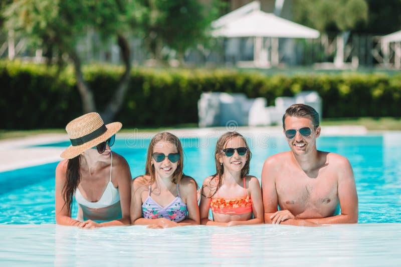 Familia de cuatro miembros feliz en piscina del aire libre foto de archivo libre de regalías