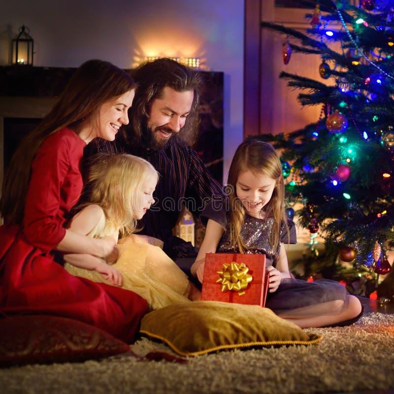 Familia de cuatro miembros feliz joven que desempaqueta los regalos de la Navidad por una chimenea fotos de archivo libres de regalías