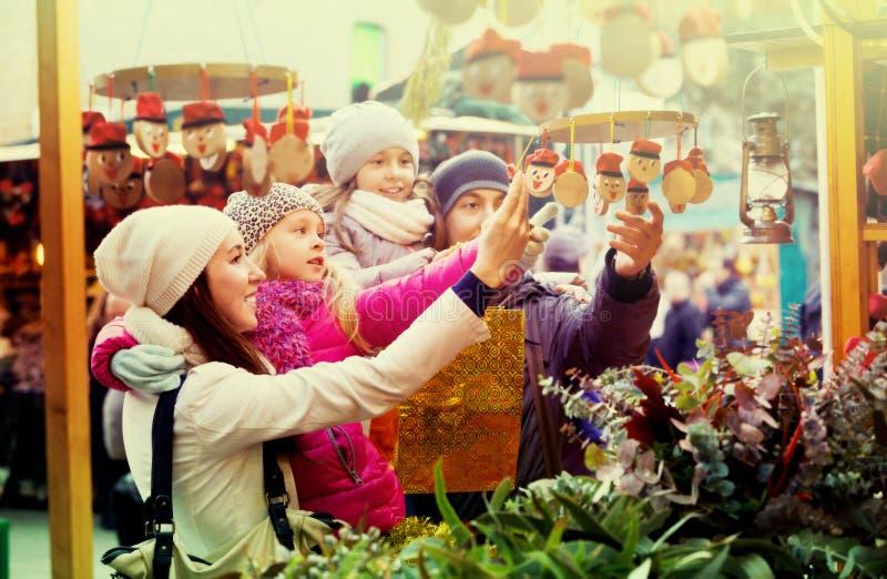 Familia de cuatro miembros feliz que compra Caga Tio Foco en la niña imagenes de archivo