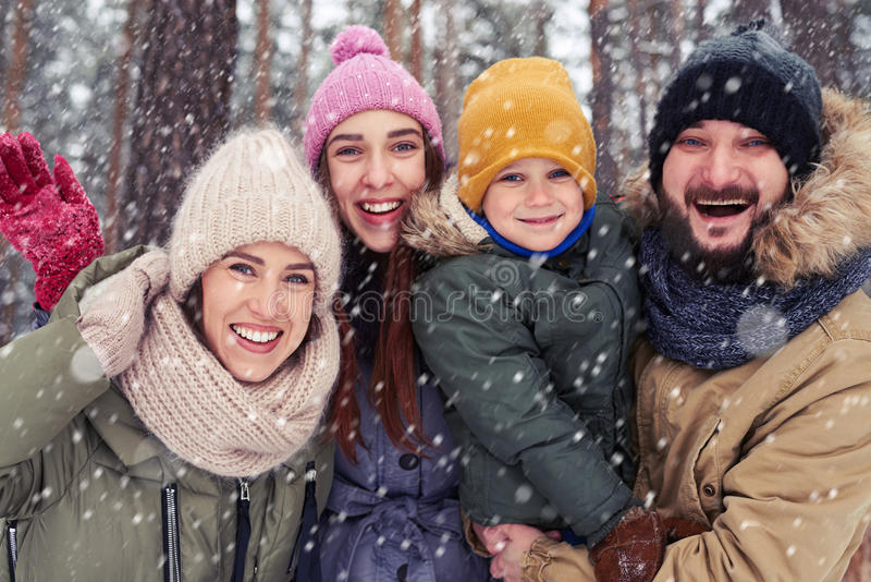 Familia de cuatro miembros feliz que se coloca en el bosque nevoso en invierno imagen de archivo