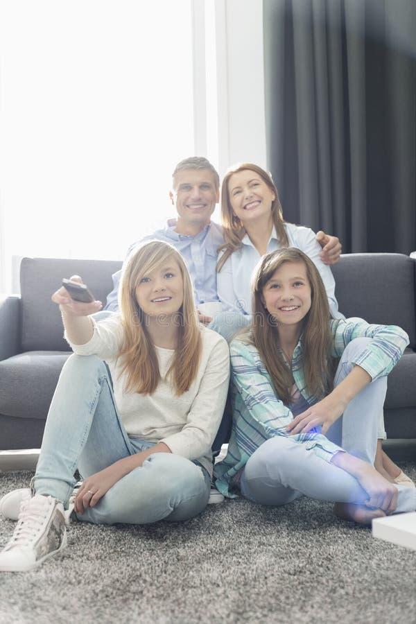 Familia de cuatro miembros feliz que ve la TV junto en casa fotografía de archivo libre de regalías