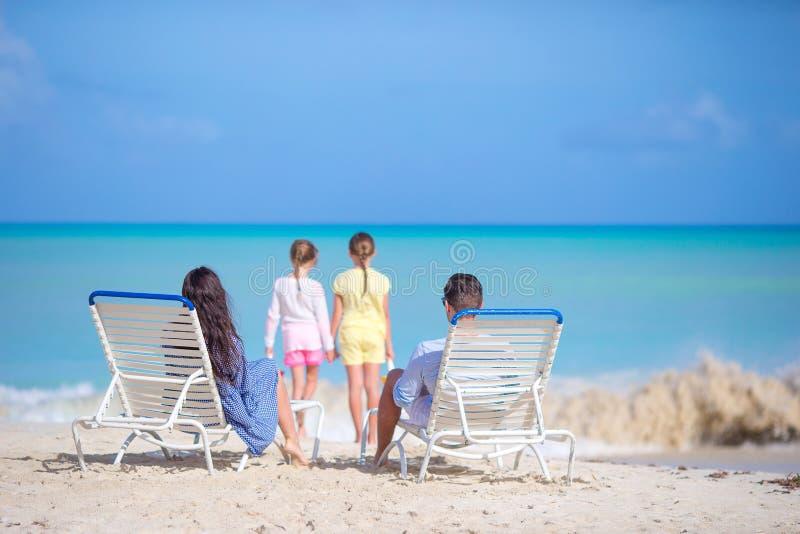 Familia de cuatro miembros hermosa feliz en la playa imágenes de archivo libres de regalías