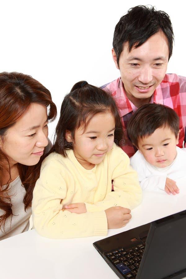 Familia de cuatro miembros japonesa en el ordenador portátil imagen de archivo libre de regalías