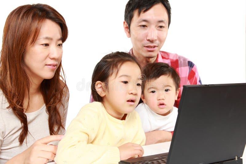 Familia de cuatro miembros japonesa en el ordenador portátil imagen de archivo
