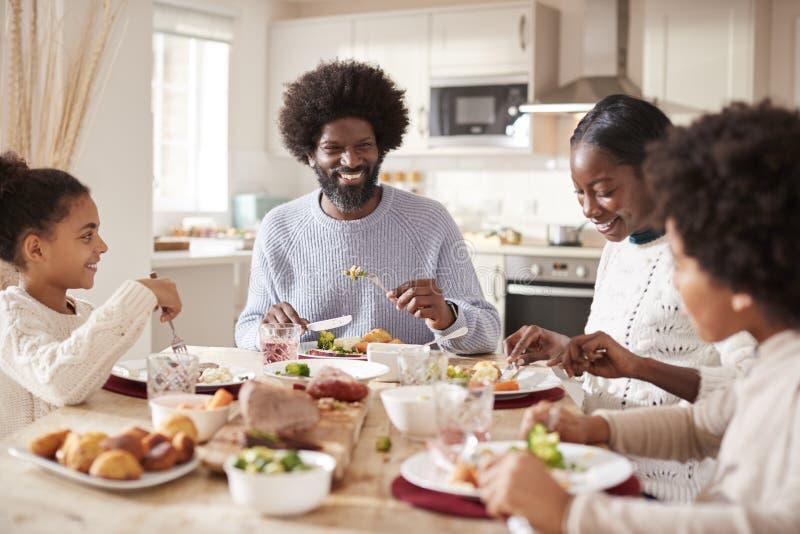 Familia de cuatro miembros joven de la raza mixta feliz que come la cena de domingo junto, vista delantera foto de archivo libre de regalías