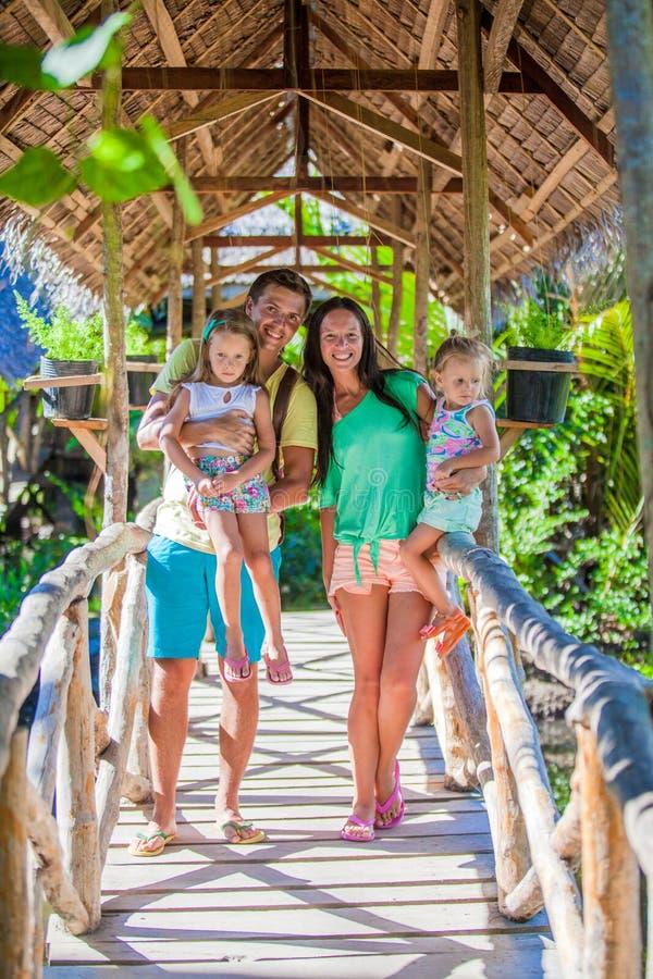 Familia de cuatro miembros joven que camina en parque de imagen de archivo