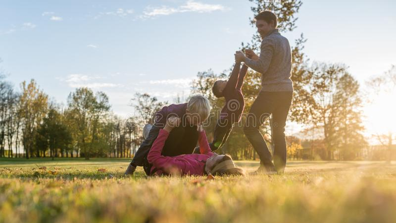Familia de cuatro miembros joven que juega en parque del otoño imagenes de archivo