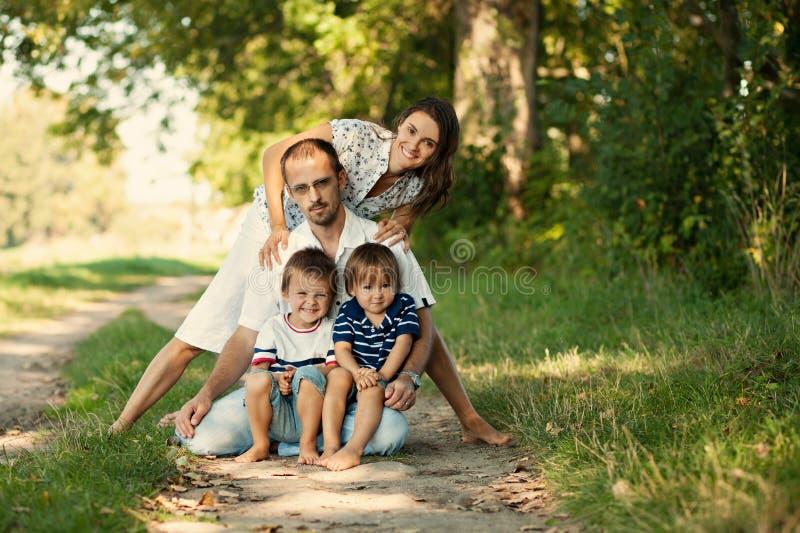 Familia de cuatro miembros linda en el parque fotografía de archivo