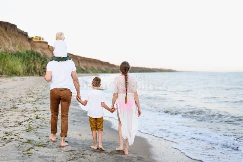 Familia de cuatro miembros que camina a lo largo de la costa padres y dos hijos Visi?n posterior fotos de archivo