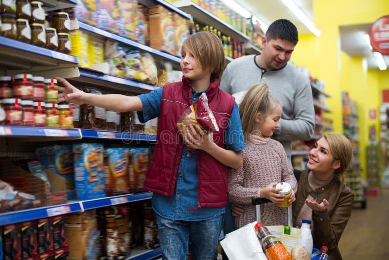 Familia de cuatro miembros que compra comida imagen de archivo