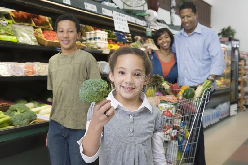 Familia de cuatro miembros que hace compras en supermercado fotos de archivo libres de regalías
