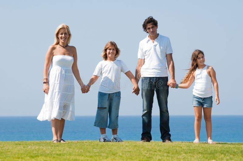 Familia de cuatro miembros que lleva a cabo las manos imagen de archivo