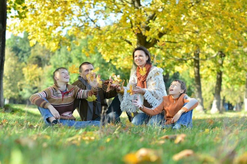 Familia de cuatro miembros que plantea la sentada en hierba fotos de archivo libres de regalías
