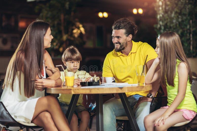 Familia de cuatro miembros que tiene gran tiempo en un restaurante fotografía de archivo