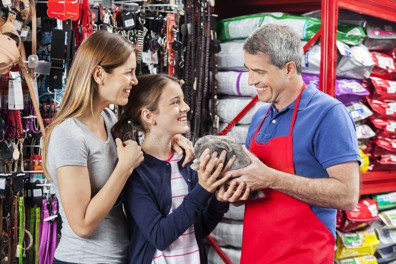 Familia de Giving Rabbit To del vendedor en la tienda del animal doméstico imagenes de archivo