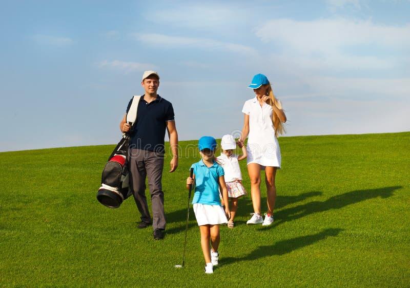 Familia de jugadores de golf en el curso imágenes de archivo libres de regalías