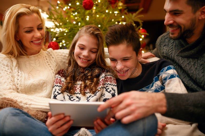 Familia de la diversión del tiempo de la Navidad con la tableta digital imagenes de archivo