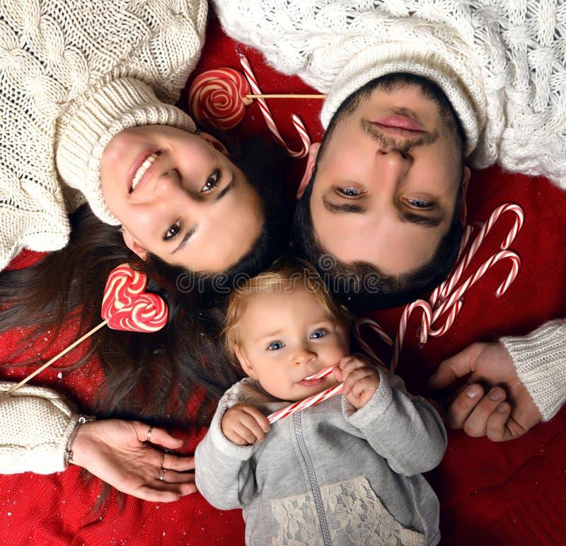 Familia de la Navidad con el niño infantil del pequeño bebé que miente en el piso imagen de archivo