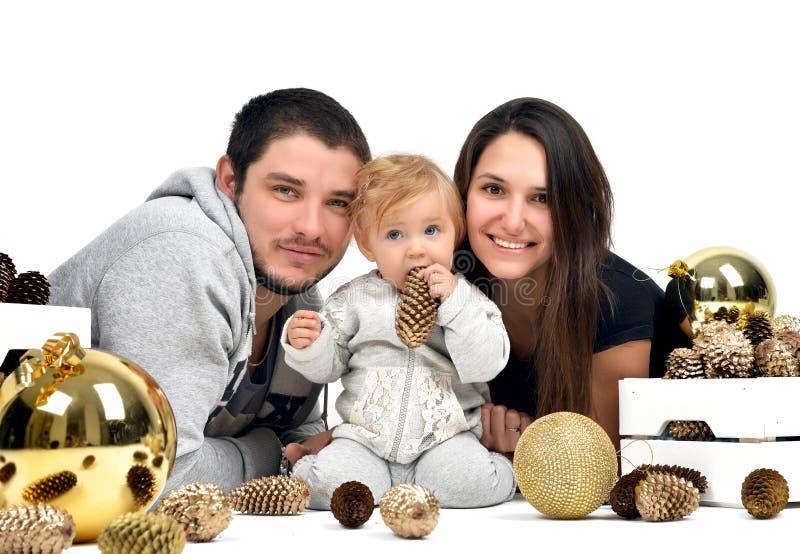 Familia de la Navidad con la pequeños conos y bola de abeto del niño y del oro del bebé fotografía de archivo