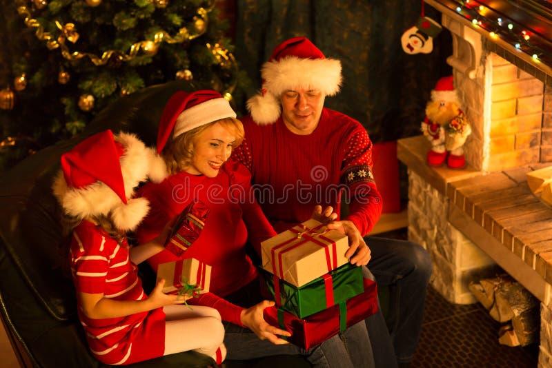 Familia de la Navidad en sombreros rojos con las cajas de regalo imagenes de archivo