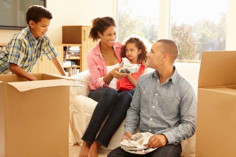Familia de la raza mixta en nuevo hogar fotografía de archivo