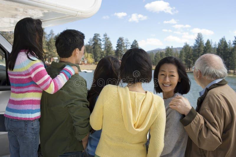 familia de la Tres-generación que mira la opinión de la parte posterior del lago foto de archivo libre de regalías