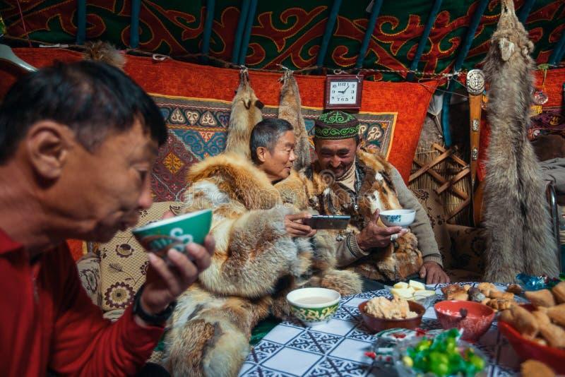 Familia de los Kazakhs de cazadores con la búsqueda del interior de las águilas de oro su el Yurts mongol fotografía de archivo