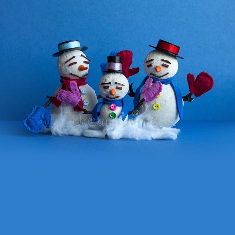 Familia de los muñecos de nieve en fondo azul Caracteres cómicos del muñeco de nieve de Navidad con las bufandas de las manoplas  imágenes de archivo libres de regalías