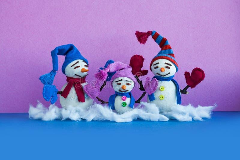Familia de los muñecos de nieve en fondo púrpura azul Caracteres cómicos del muñeco de nieve de Navidad con las bufandas de las m imagen de archivo