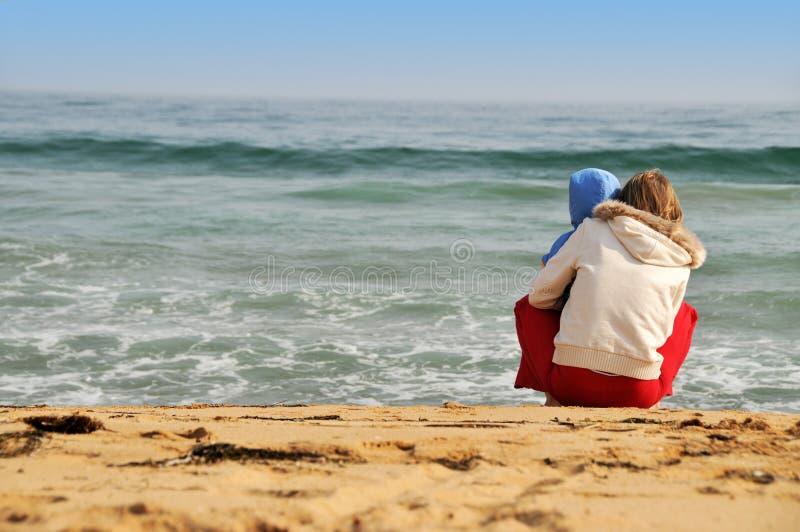 Familia de madre con el bebé en la playa del mar foto de archivo libre de regalías