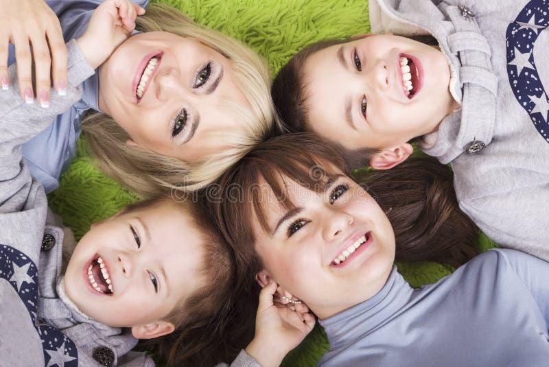 Familia de madre feliz y de niños que se relajan en verde imagen de archivo libre de regalías