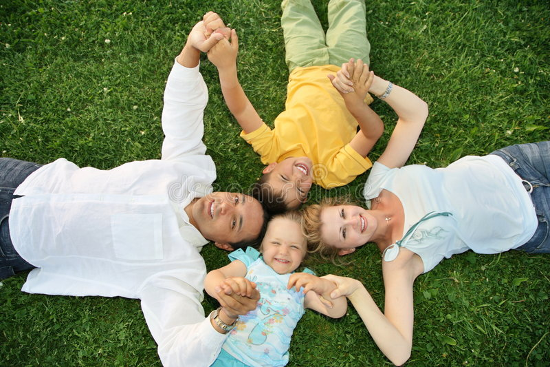 Familia de mentira en hierba fotografía de archivo libre de regalías