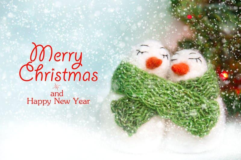 Familia de muñecos de nieve felted cariñosos felices blancos de las lanas con la bufanda hecha punto verde cerca del árbol de nav imagen de archivo libre de regalías