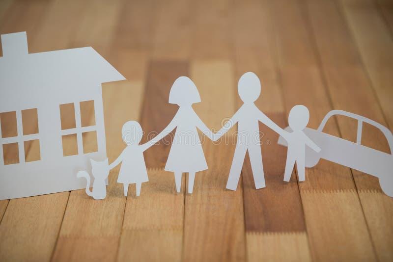 Familia de papel del recorte con la casa y el coche foto de archivo
