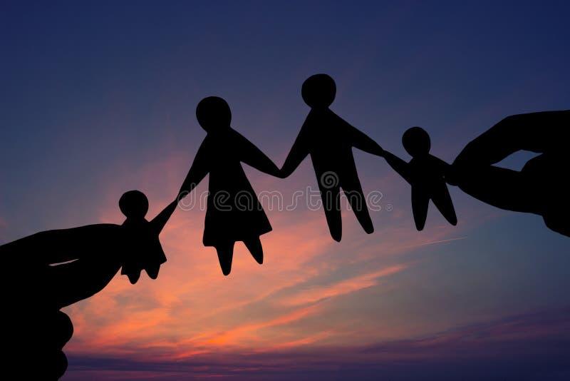 Familia de papel en dos manos contra el fondo del cielo fotos de archivo libres de regalías