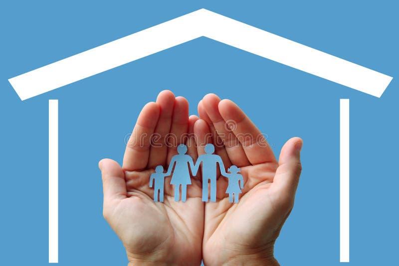 Familia de papel en manos con el hogar en concepto azul del bienestar del fondo imágenes de archivo libres de regalías