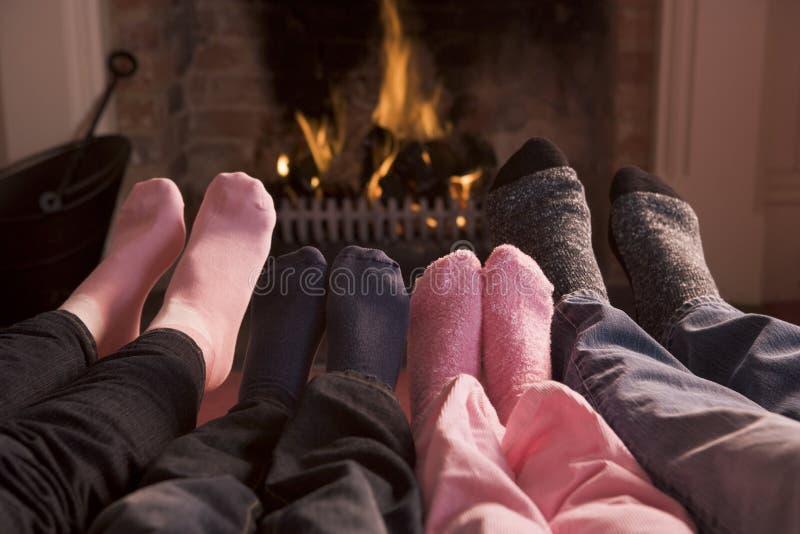 Familia de pies que se calientan en una chimenea