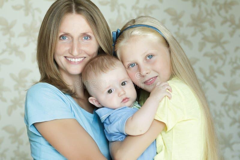 Familia de retrato interior sonriente y de abrazo de tres de la gente fotos de archivo