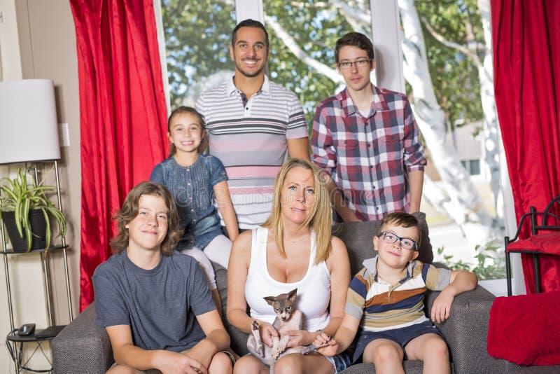 Familia de seis en el sofá en la sala de estar fotografía de archivo