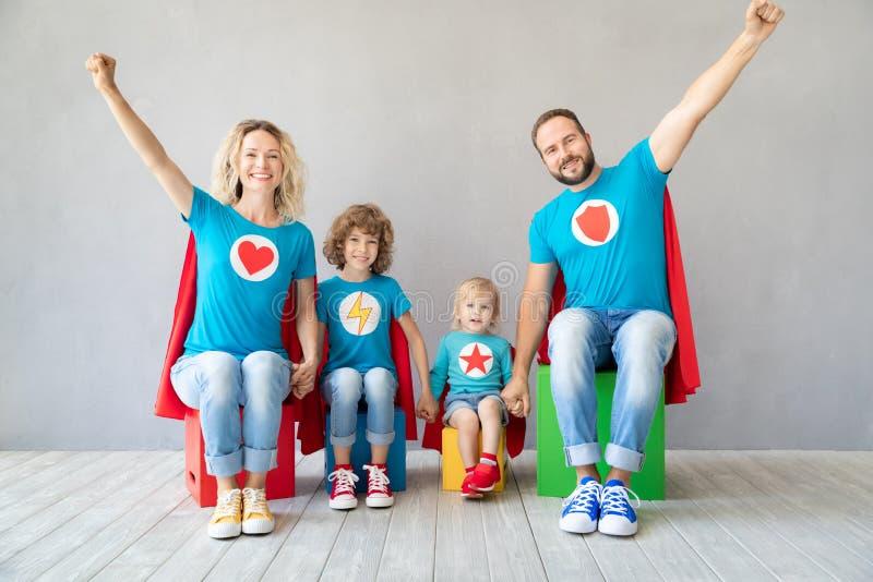 Familia de super héroes que juegan en casa fotos de archivo