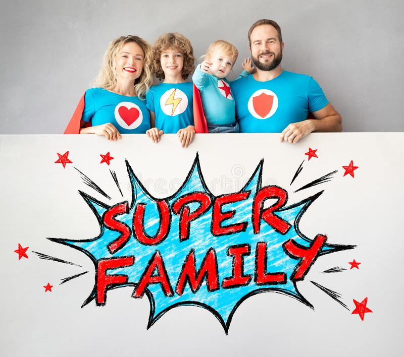 Familia de super héroes que sostienen la bandera fotos de archivo