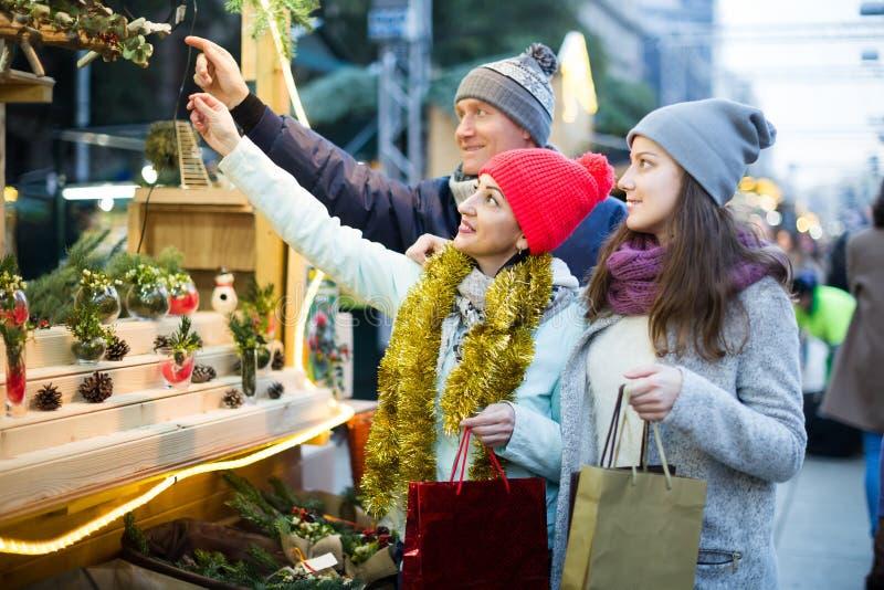 Familia de tres con el adolescente que elige decoraciones florales fotografía de archivo libre de regalías