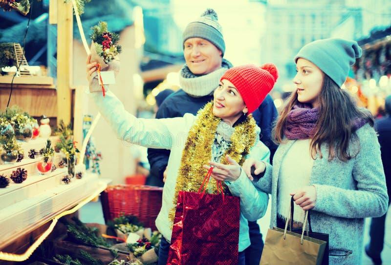Familia de tres con el adolescente que elige decoraciones florales imagen de archivo libre de regalías